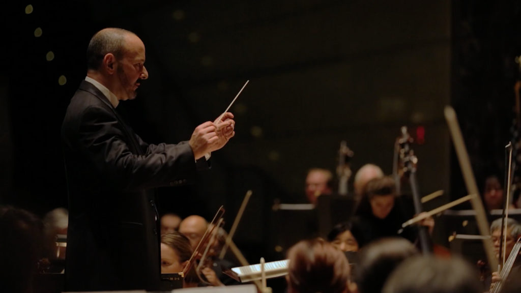 Side view of Stuart Malina conducting the orchestra.